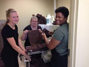 Mallory, LMT, Holly, Laundry Assistant, and Tiffany, LMT/Receptionist work together to keep up with the linens!