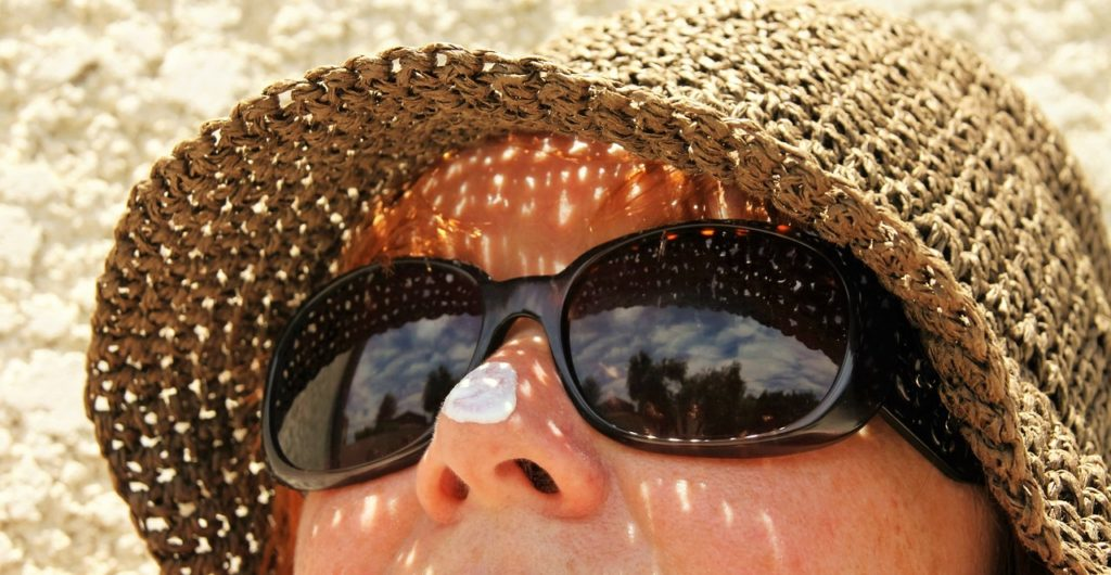Woman with hat, sunglasses, and sunscreen on her nose.