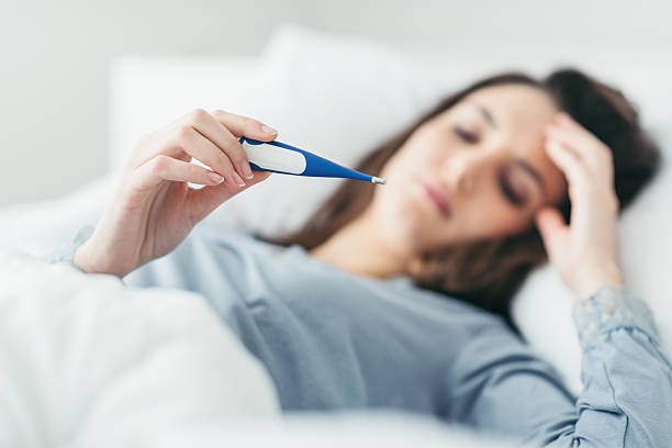 Woman looking at thermometer, laying in bed sick.